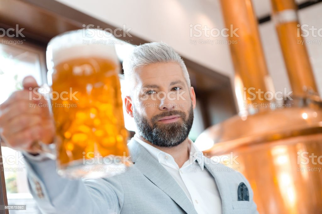 The microbrewery owner holding a beer mug in his pub The microbrewery owner standing in front to copper vat and holding beer mug, toasting at the camera. Adult Stock Photo
