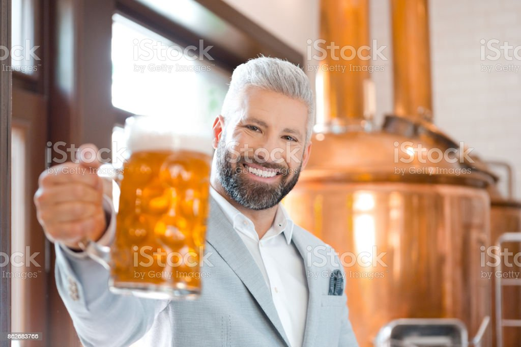 The microbrewery owner holding a beer mug in his pub The microbrewery owner standing in front to copper vat and holding beer mug, toasting at the camera. Selective focus. Adult Stock Photo