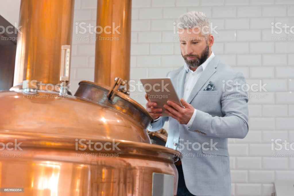 The microbrewery owner using a digital tablet in his micro brewery The microbrewery owner standing next to copper vat and using a digital tablet. Adult Stock Photo