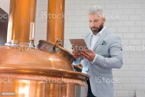 The Microbrewery Owner Using A Digital Tablet In His Micro Brewery Stock Photo - Download Image Now