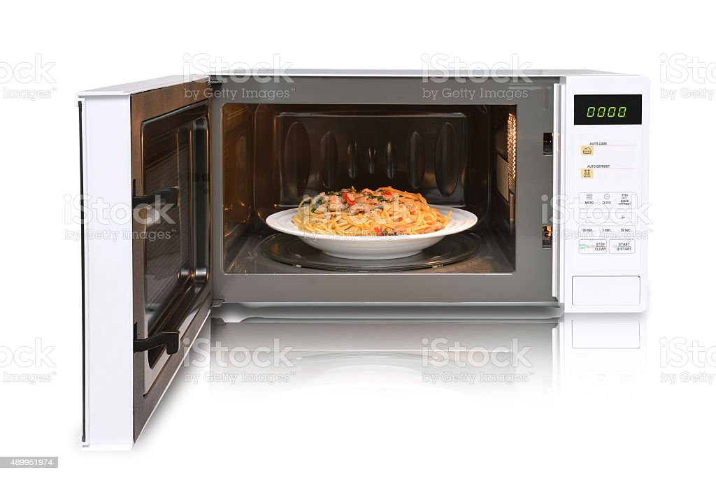 The microwave oven is warm spaghetti. stock photo