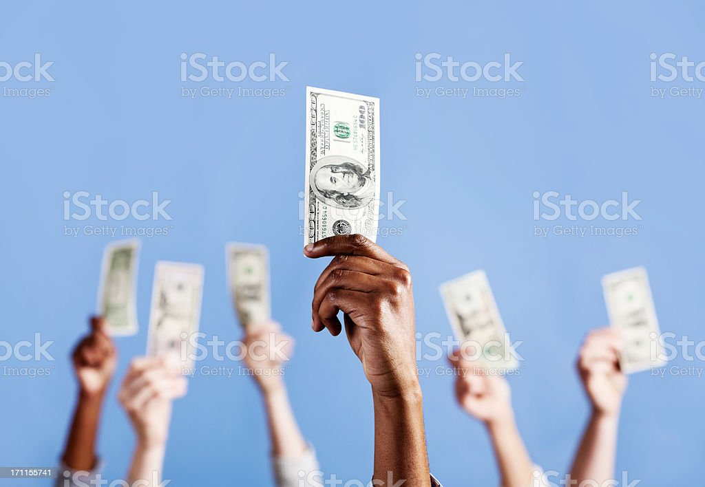 The mighty dollar! Six hands hold up US currency stock photo