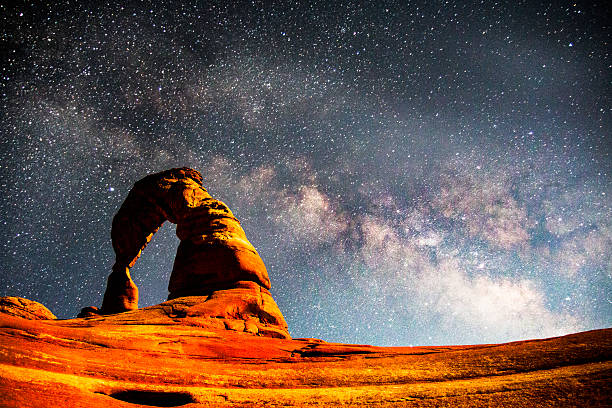 The Milky Way above Delicate Arch, Arches National Park The Milky Way above Delicate Arch, Arches National Park arches national park stock pictures, royalty-free photos & images