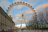 The London Eye on the South Bank taken early in the morning with two people walking.  It is a popular tourist attraction and you can see panoramic views over the City of London,  Great Britain, February 2018
