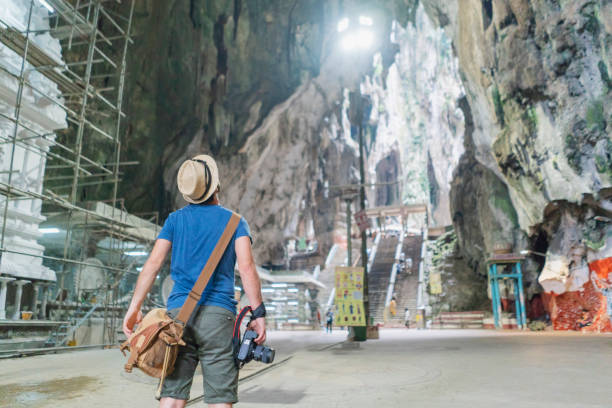 The miracle of nature Male tourist admiring the inside of Batu Caves kuala lumpur batu caves stock pictures, royalty-free photos & images