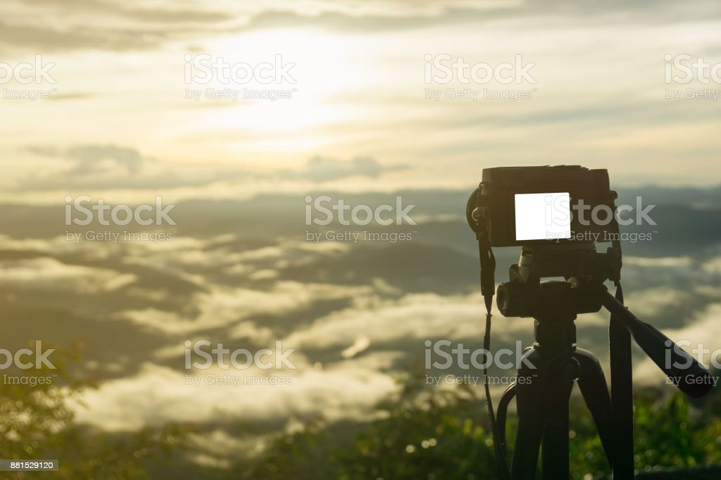 The Mirrorless camera put on the tripod for recording the viedo or capturing the beautiful mountain scenery with sun light in th morning. stock photo