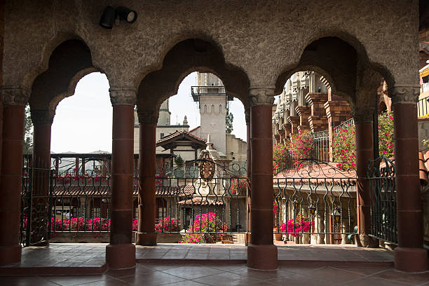The Mission Inn Arches Beautiful arches frame a view of the Mission Inn in Riverside, California. Bougainvillea bloom a brilliant magenta. The Inn is generally considered the largest Mission Revival Style building in the United States. The eclectic structure was drawn from many historical design periods, revivals, influences, and styles. Some are Spanish Gothic architecture, Mission Revival Style architecture, Moorish Revival architecture, Spanish Colonial style architecture, Spanish Colonial Revival Style architecture, Renaissance Revival architecture, and Mediterranean Revival Style architecture. inn stock pictures, royalty-free photos & images
