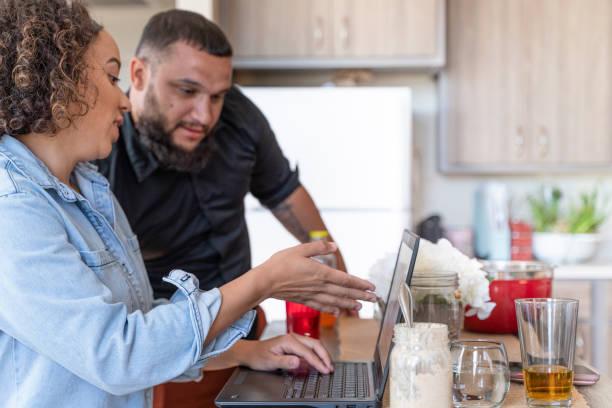 Das gemischte Rennpaar arbeitet mit einem PC-Laptop in der Küche. – Foto