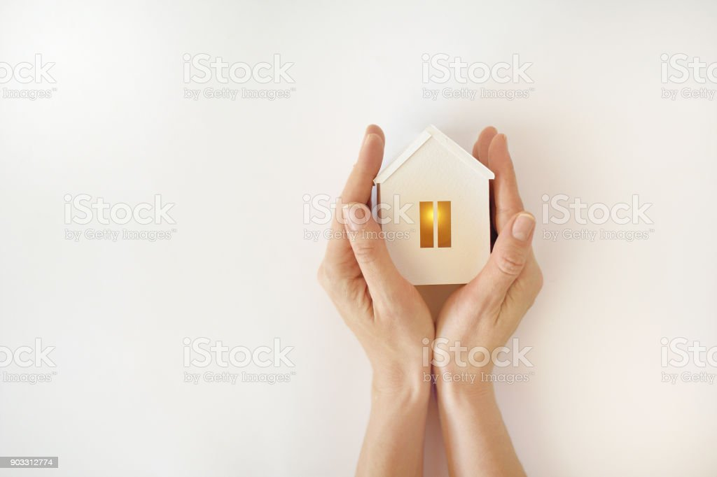 The model of the White House with warm light inside in female hands on a white background stock photo