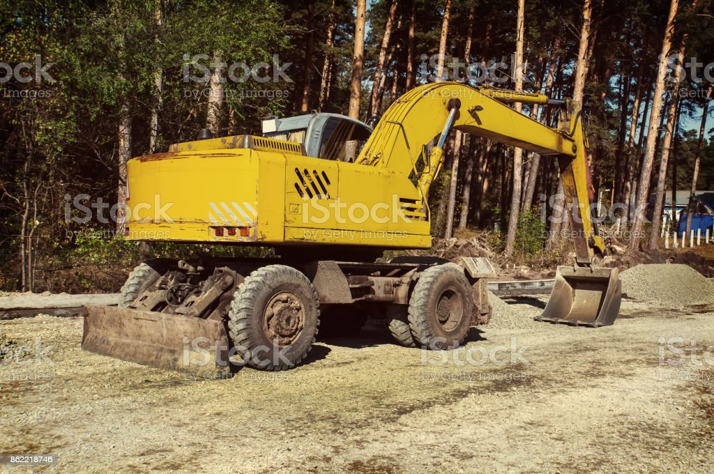 The modern excavator performs excavation work on the construction site stock photo
