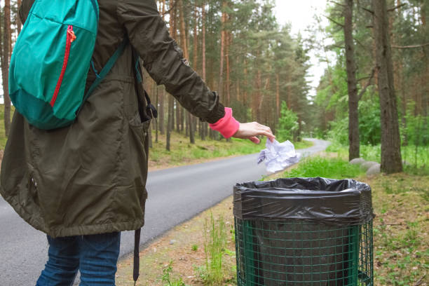 The modern woman throwing out garbage in basket . stock photo