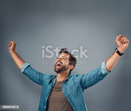 Studio shot of a handsome young man cheering against a grey background