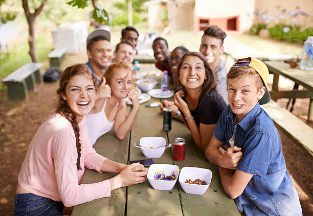 The moments we remember forever Shot of a group of teenagers having a picnic at a table in the park teenagers only stock pictures, royalty-free photos & images