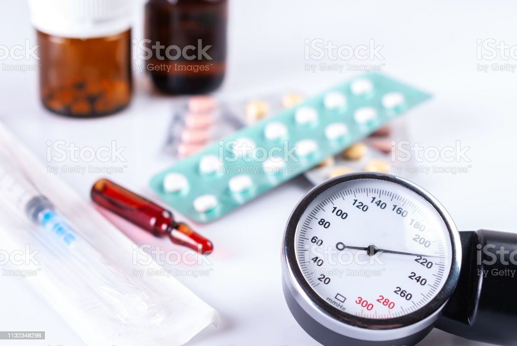 O monitor de pressão arterial, uma seringa, ampolas e frascos com preparações - foto de acervo