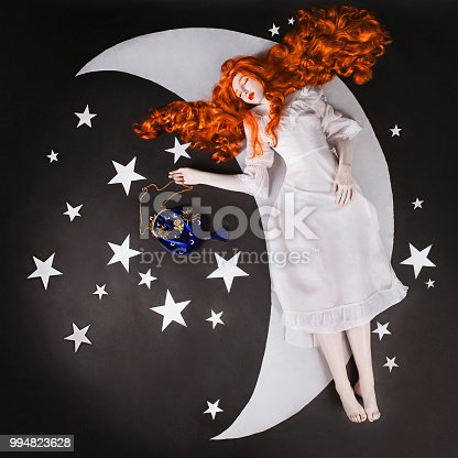 478539432 istock photo The moon and the stars. Young fairy woman with very long hair in white dress on black background. A beautiful girl with pale skin. Renaissance fairy princess sleep on the moon. Sweet dream 994823628