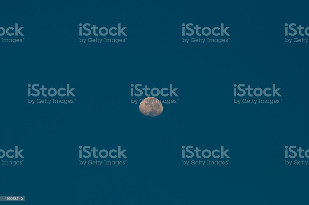 The Moon on background against blue sky. stock photo