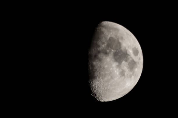 The moon rises high in the sky stock photo
