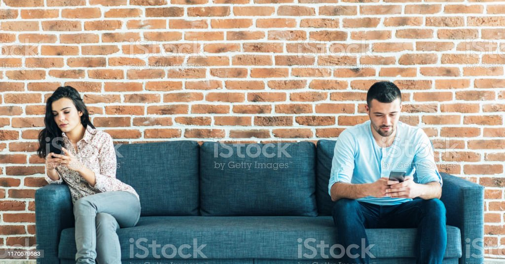 The more connected, the more divided Man and woman sitting in the opposite side of the sofa and texting using smartphones 20-29 Years Stock Photo