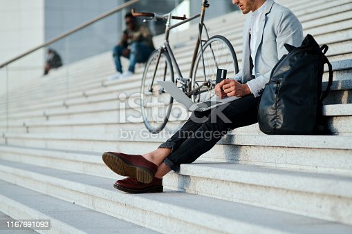 Shot of a young businessman using a laptop and credit card on the steps in a city