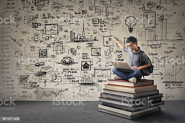 Young Asian boy with nerdy black glasses sitting on a book hill, drawing his ideas creatively on the wall behind him while looking at his computer.