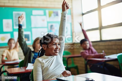 Shot of young children raising their hands in a classroom