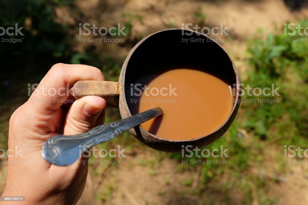 The Morning coffee in the glass from natural coconut shells on woman hands stock photo