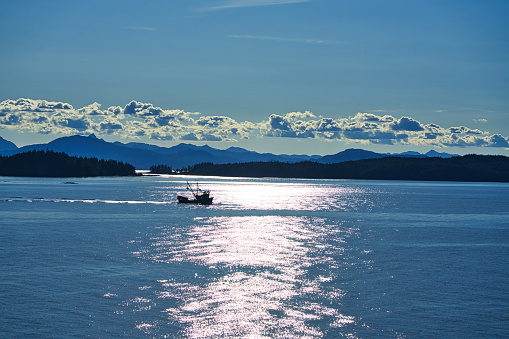 The morning sunlight mapped the surface of the lake. The work boat is operating. Ketchikan, Alaska is truly the beginning of the
