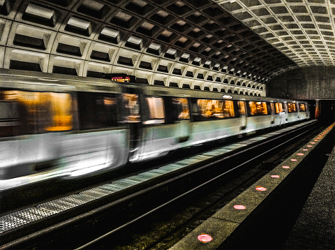 Subway train traveling through station