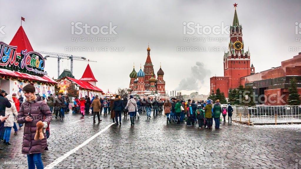 The Moscow Kremlin, crowd of people walking in the Red Square with the unic landscape of  of St. Basil's Cathedral, Lenin's mausoleum and the Spasskaya tower. stock photo