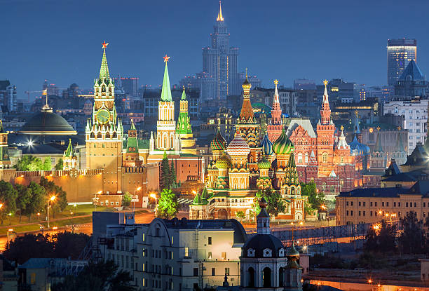 The Moscow Kremlin Night view of the Moscow Kremlin, Red Square and St. Basil's Cathedral from the residential house rooftop. kremlin stock pictures, royalty-free photos & images