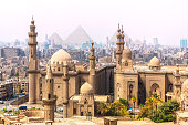The Mosque-Madrassa of Sultan Hassan and the Pyramids in the background, Cairo, Egypt.