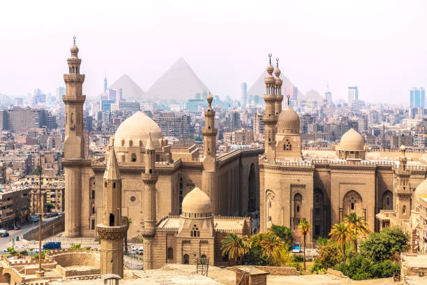 The Mosque-Madrassa of Sultan Hassan and the Pyramids in the background, Cairo, Egypt The Mosque-Madrassa of Sultan Hassan and the Pyramids in the background, Cairo, Egypt. minaret stock pictures, royalty-free photos & images