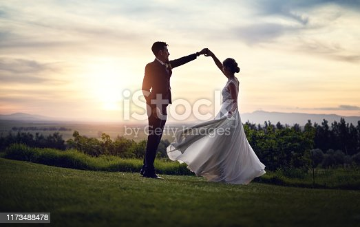 Shot of a happy young couple dancing outdoors at sunset on their wedding day