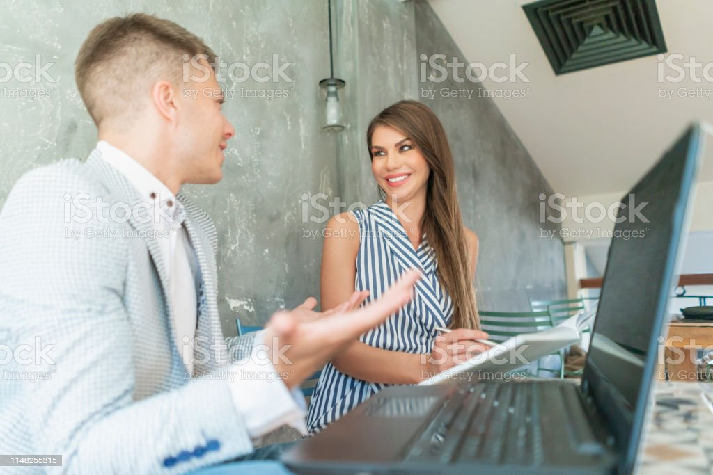 Handsome young Caucasian ethnicity businessman working on a laptop...