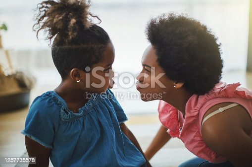Mother and daughter playing on the floor. They sending kisses to each other and joke around.