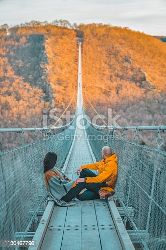 Photo of young couple sitting on a hanging bridge in Germany during the summer day, suspension rope bridge. Young female sitting with her boyfriend outdoor and admiring view Travel Lifestyle concept with rope bridge background and sunset. Young woman and man hanging rope bridge with sky as background. Leisure extreme activity at autumn day. Beautiful tourist on an excursion.
