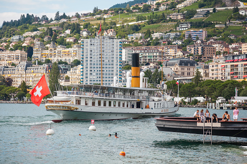 The most beautiful  steam boat called La Suisse with Swiss flag waving at the stern approaching Montreux pier on Swiss Riviera, Vaud, Switzerland