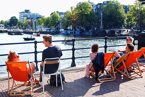 People sitting on deck chairs talking and relaxing at al fresco summer terrace by the Amstel river on the
