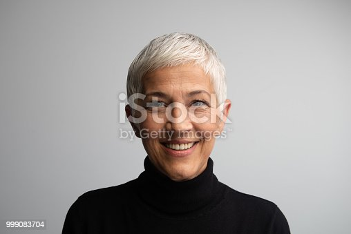 Beautiful 50+ woman posing in studio in front of grey background.