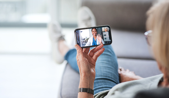 Shot of a senior woman using a smartphone to make a video call with her doctor on the sofa a home