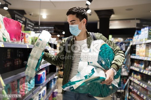 Young Man shopping in a supermarket, breathing through a medical mask because of the danger of getting the flu virus, influenza infection. Corona virus pandemic concept. Covid-19 virus!