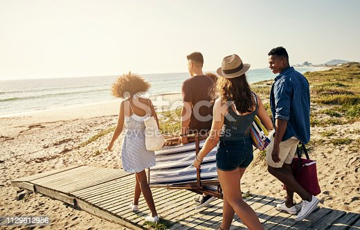 Shot of a group of friends spending time together at the beach