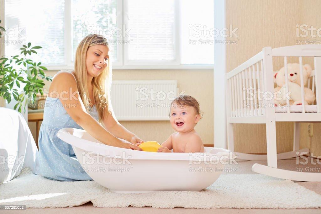 Die Mutter badet das Baby im Badezimmer im Zimmer. – Foto