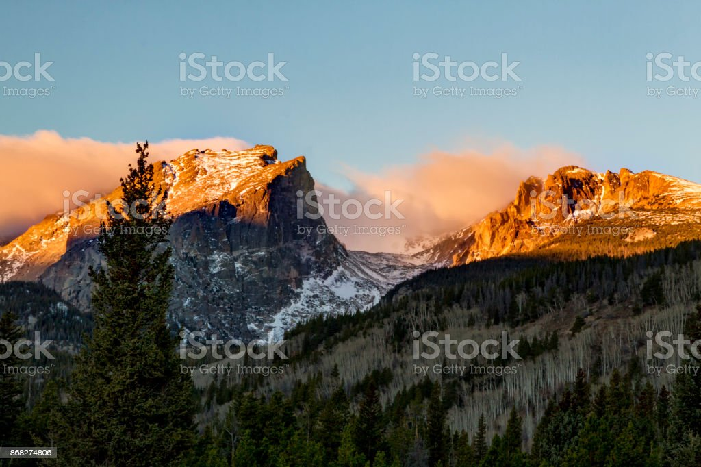 The Mountain Peaks glow at sunrise in Rocky Mountain National Park Colorado stock photo