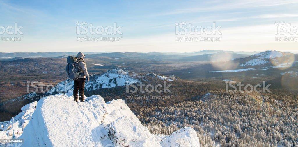 El alpinista subió a la cima de la montaña, caminante de hombre de pie en la cima de la roca cubierta con hielo y nieve, vista desde atrás. Temporada de invierno. - foto de stock