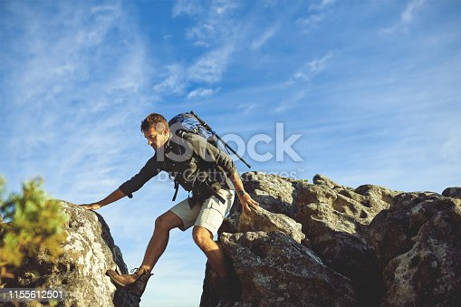 Shot of a young man hiking up a mountain