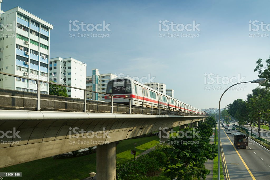 The MRT train on overpass tracks next to buildings and road royalty-free stock photo