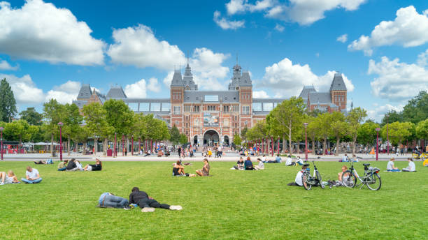 the museum square in front of the Rijksmuseum Amsterdam, The Netherlands - 23th July 2020 - Tourists sitting on the grass of the museum square in front of the Rijksmuseum (federal museum) in the center of Amsterdam rijksmuseum stock pictures, royalty-free photos & images