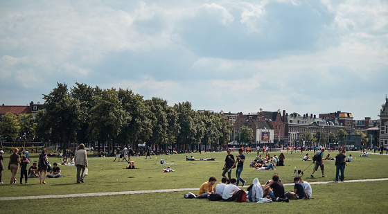 Amsterdam, Netherlands - 4 August, 2019: People walking and relaxing around The Museumplein (Museum square), a public space in the Museumkwartier neighborhood on sunny day