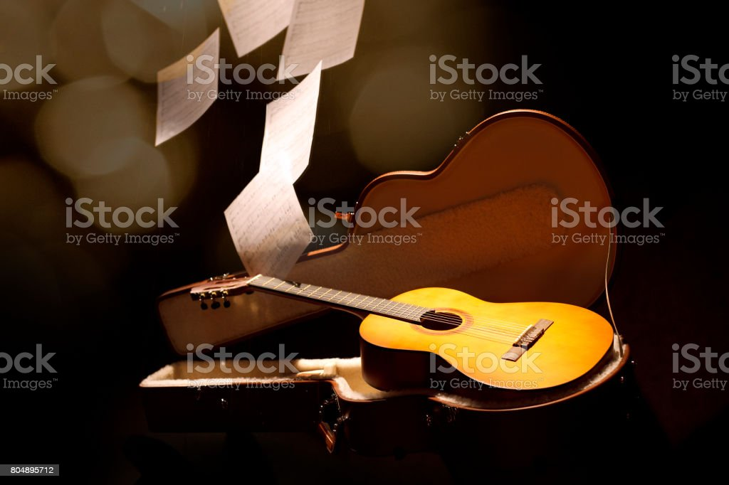 The music sheet falls on the Guitar stock photo